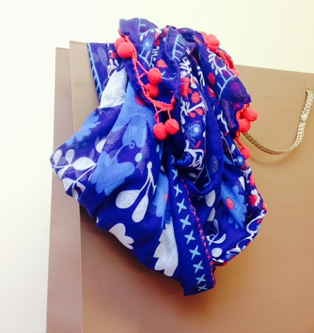 scarf draped from luxury carrier bag